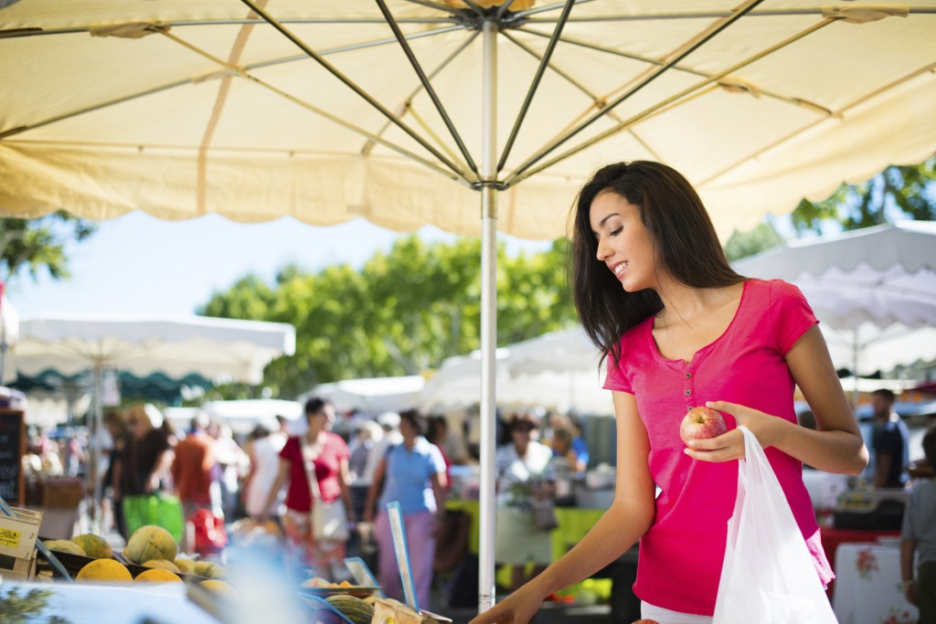 cheerful healthy young woman shopping in farmers market buying fresh organics fruits and vegetables