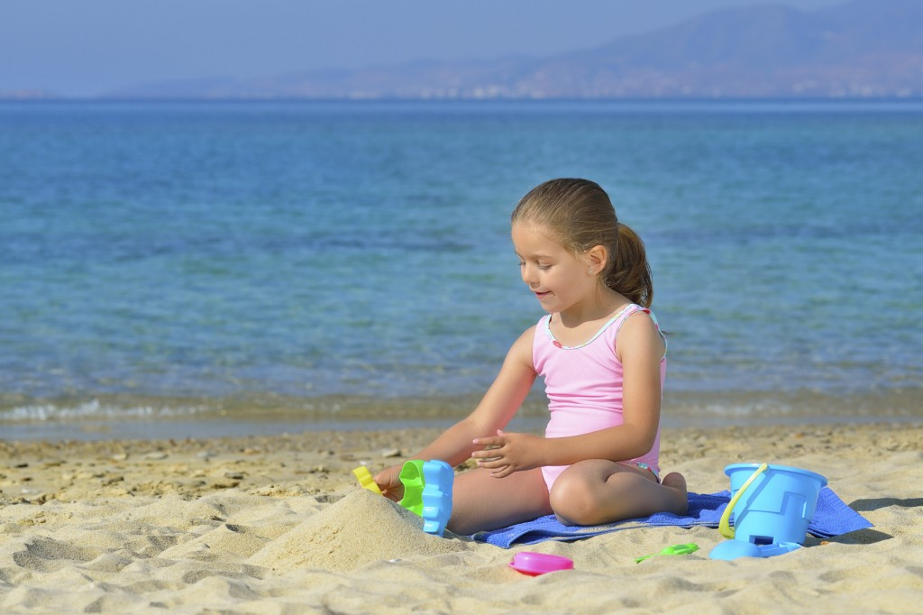 Adorable toddler girl playing with her toys at the beach
