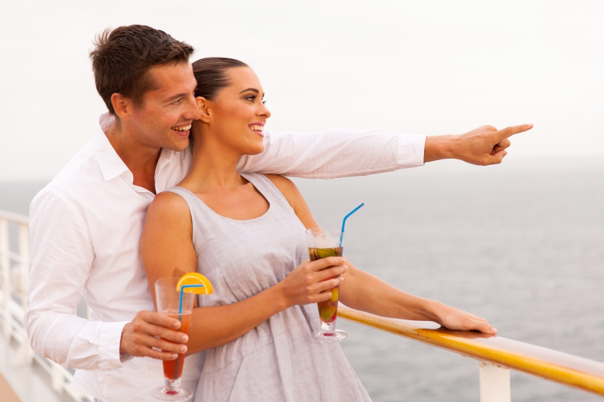 cheerful couple with cocktails enjoying sea view from cruise ship