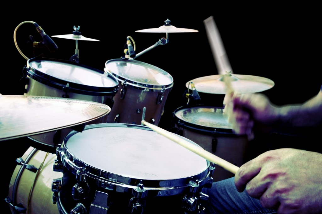 drummer playing isolated over black background