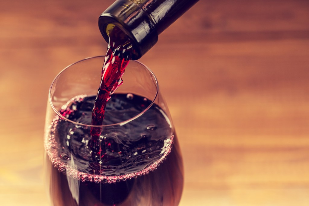 Pouring red wine into the glass against wooden background