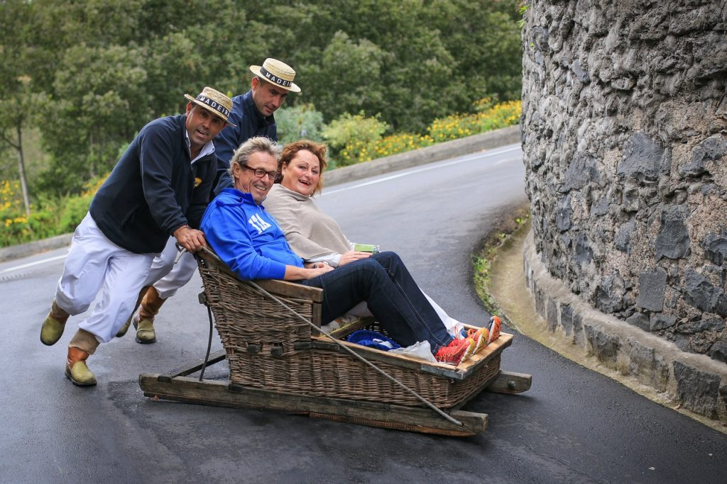 Funchal, Portugal - November 11, 2015: Tourists enjoying a ride on toboggan (traditional sled) through the streets of Madeira's capital city.