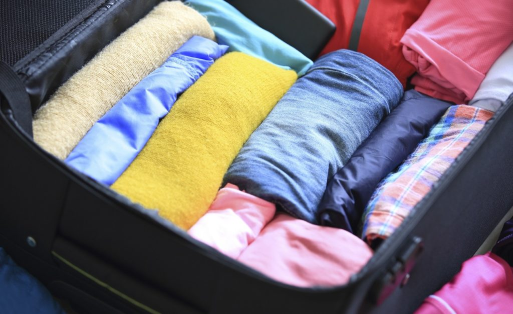 packed suitcase with rolled up clothes