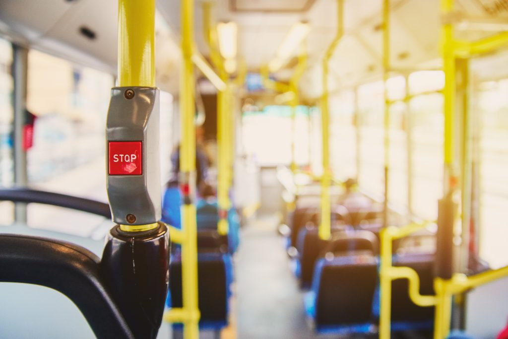 Red button STOP on the bus. Bus with yellow handrails and blue seats. Photo with the sun effect, glare on the lens from the light. Spacious interior of the bus, bright button with focus