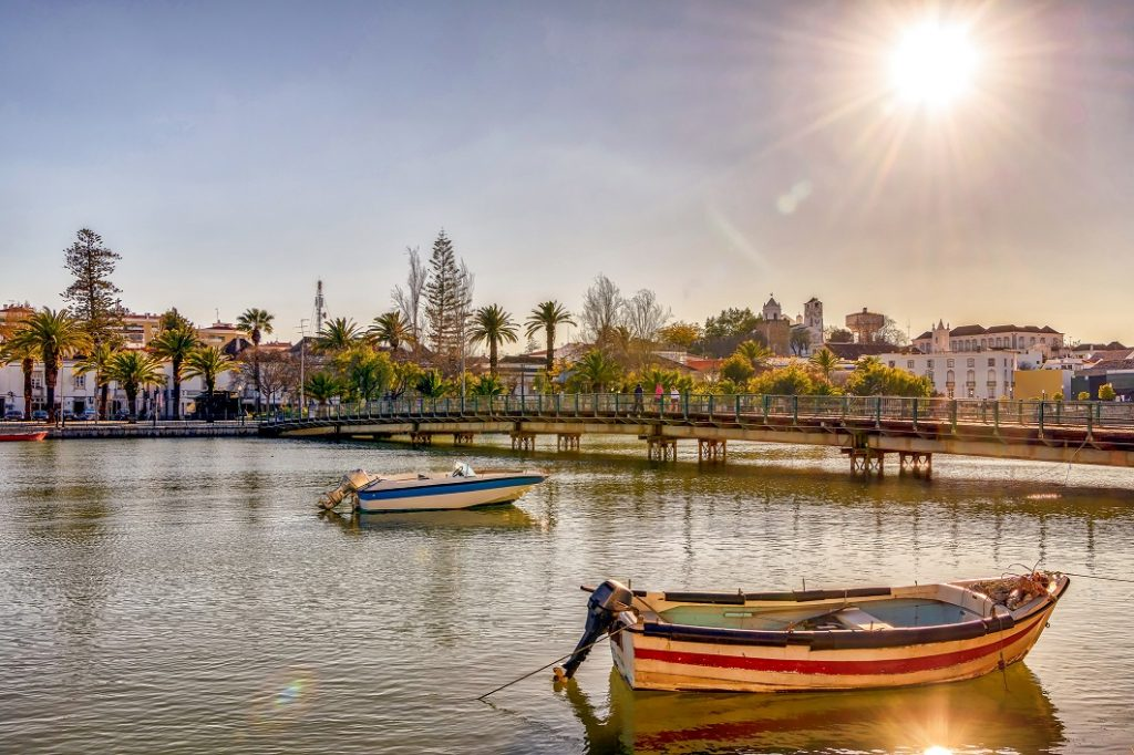 Beautiful post card, with boats on serene Gilao river, and the sun shining over picturesque Tavira, a popular tourist destination in southern Portugal.
